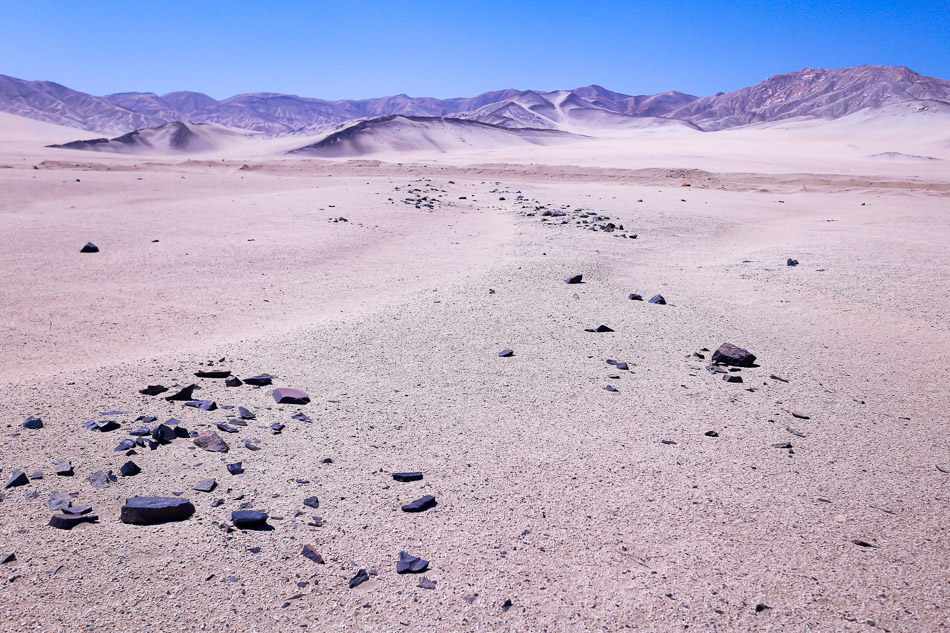 "Absolute desert, Atacama, Chile. The phrase ""absolute desert"" describes the barrenness found once one moves down from the mountains into the Atacama Desert. ""Below about 3,000 meters in altitude, plants become so widely spaced that they disappear from the landscape."